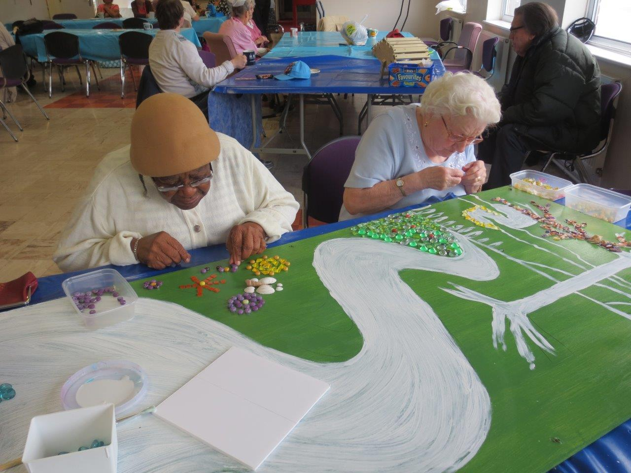 Two members sitting at a table creating the mosaic picture